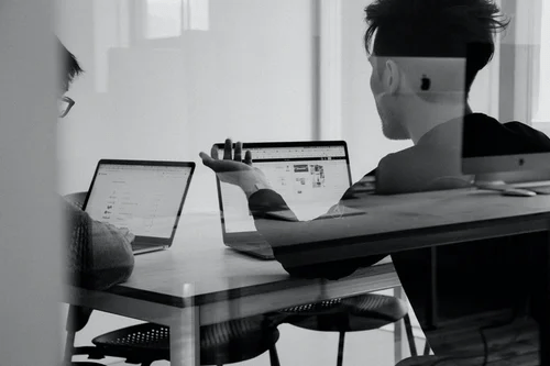 two people facing a laptop