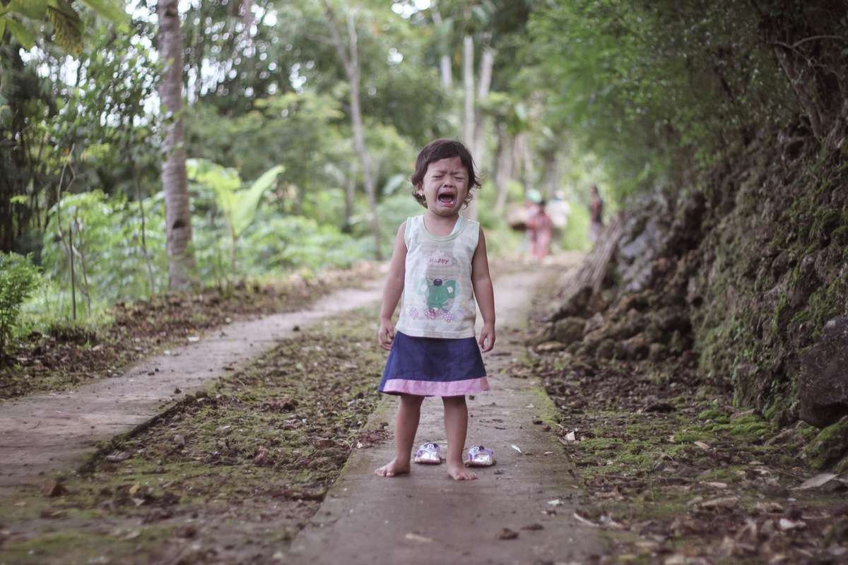 A toddler cries with despair in a wooded area.